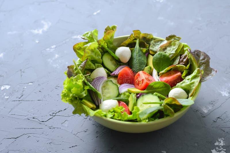 sund mat Grönsaksallad med grönsallat-, tomat-, avokado-, gurka-, spenat- och mozzarellaost med kopieringsutrymme royaltyfria foton