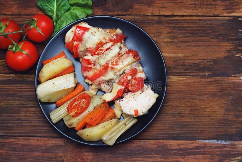 Sund mat - grillad höna med grönsaker på ett träbräde med Tomatoe filial- och kopieringsutrymme arkivfoto