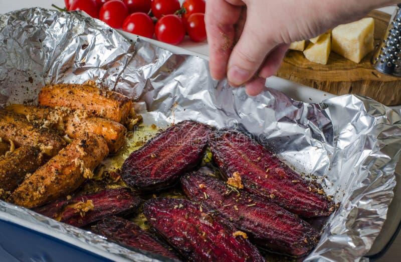 sund mat Kryddade beta och morötter lägger i en laga mat form bredvid det tomat-, parmesan-, vitlök- och ostrivjärnet royaltyfri foto