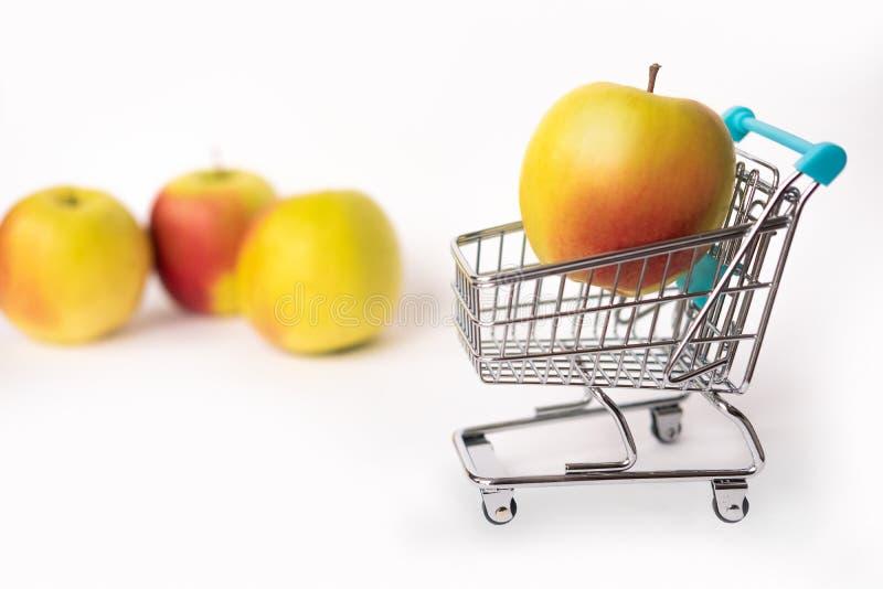 Sund mat och riktig näring Apple i en shoppa vagn bakgrund isolerad white kopiera avstånd royaltyfri foto