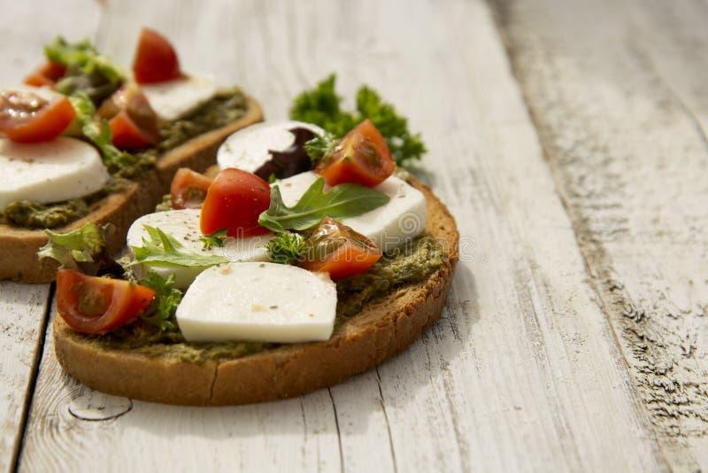 sund mat Rosta sm?rg?sen med mozzarellaen, k?rsb?rsr?da tomater och pesto, ljus tr?bakgrund Sund frukost, mellanm?l kopia arkivfoton