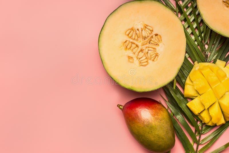 Sund mat, tropiska frukter, mango, melon på ett monsterablad med smoothies på en rosa bakgrund, utrymme för den lekmanna- textläg royaltyfria foton