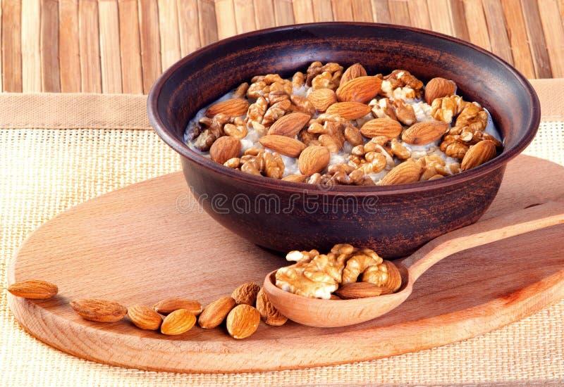 sund mat Valnötter och mandlar med mjölkar i lerabunke på en träbakgrund royaltyfri fotografi