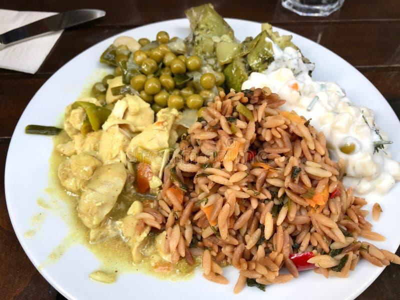 Sund matplatta för turkisk stil med kornOrzo ris, höna för currysås, gröna ärtor och pastasallad på restaurangen fotografering för bildbyråer