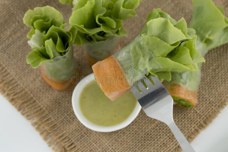 Sund matsalladrulle med den krabbapinnen och grönsaken Äta med den havs- dressingen på bakgrund för gammal påse arkivfoto