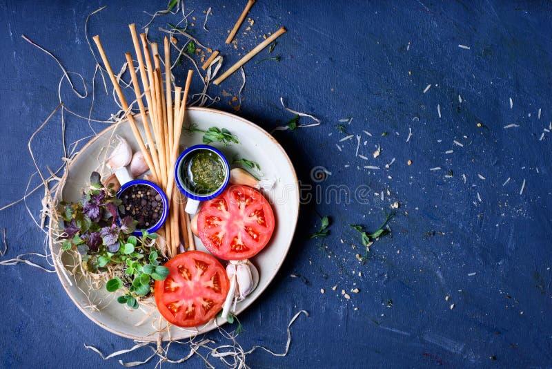 Sund mellanmålplatta, tomater, groddar, brödpinnar appetisers arkivfoto