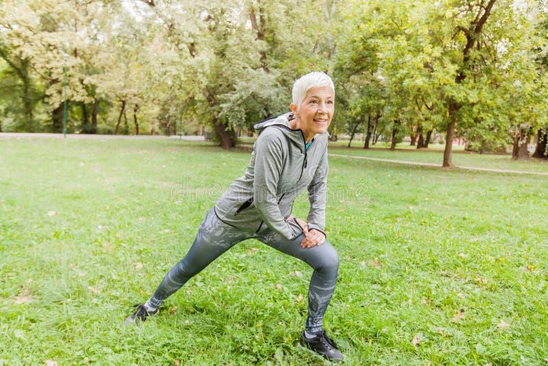 Sund mellersta åldrig kvinna som sträcker övning i natur fotografering för bildbyråer