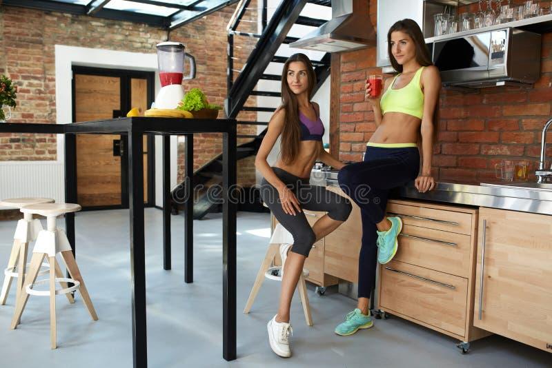 sund näring Konditionkvinnor i Sportswear som dricker smoothien royaltyfri bild