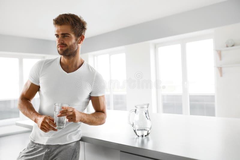 sund näring Man som dricker exponeringsglas av sötvatten i morgon arkivfoton