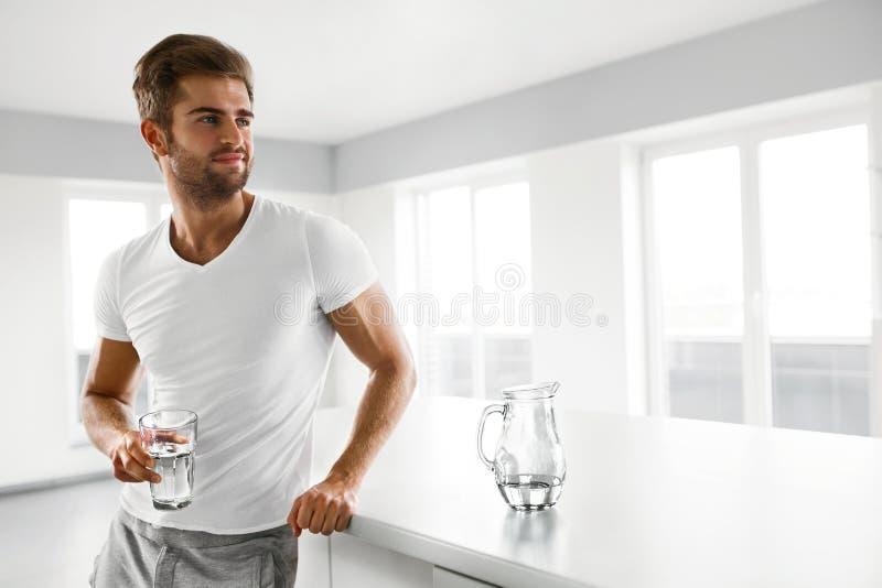 sund näring Man som dricker exponeringsglas av sötvatten i morgon arkivbild