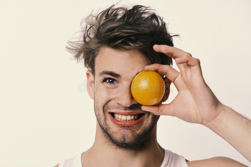 Sund näring och bantar begrepp Man med det orange ögat för beläggning en i hans hand royaltyfria foton