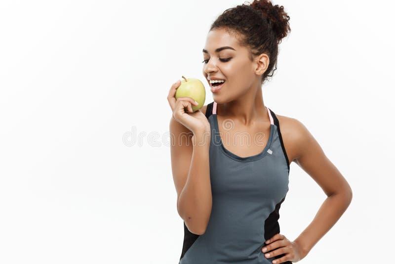 Sund och konditionbegrepp - härlig amerikansk afrikansk dam i grå konditionkläder som äter det gröna äpplet Isolerat på royaltyfri bild