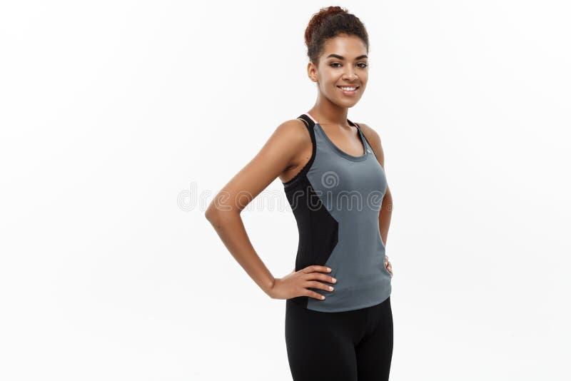 Sund och konditionbegrepp - härlig amerikansk afrikansk dam i konditionkläder som är klar för genomkörare Isolerat på vit arkivbilder