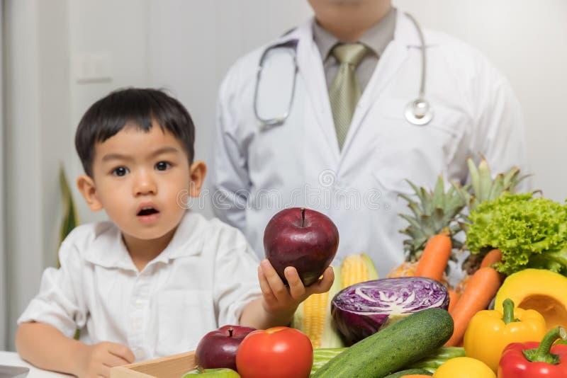 Sund och näringbegrepp Lura att lära om näring med doktorn att välja att äta nya frukter och grönsaker Ung asiat arkivbilder
