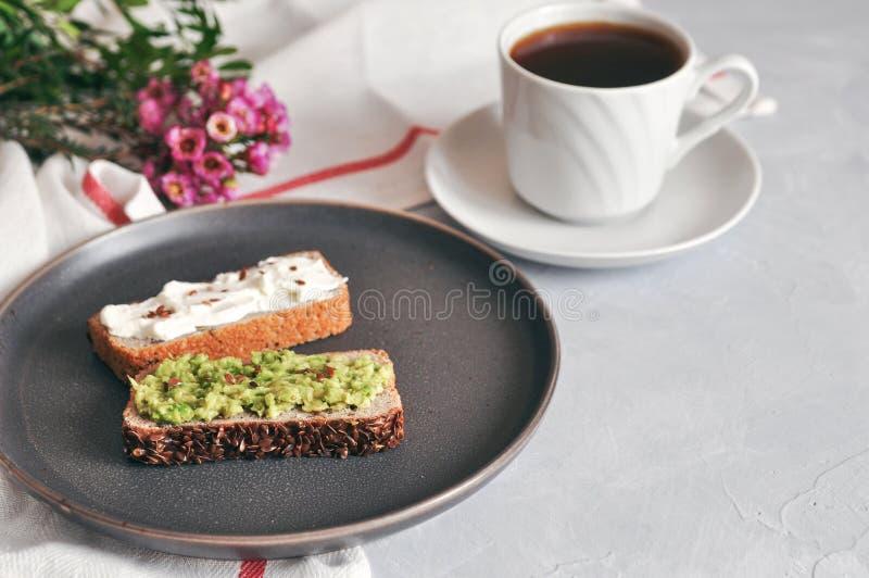 Sund och riktig frukostsmörgås med avokadot och hemlagat bröd på sourdough av grön bovete med linfrö, solros royaltyfria bilder