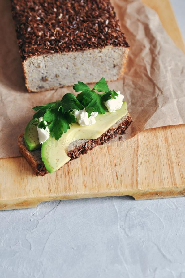 Sund och riktig frukostsmörgås med avokadot och hemlagat bröd på sourdough av grön bovete med linfrö, solros royaltyfri foto