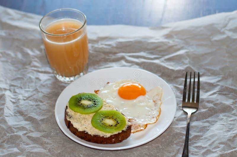 Sund och smaklig frukost, fruktsaft, wholegrain smörgås med kiwin och stekt ägg på den vita plattan fotografering för bildbyråer