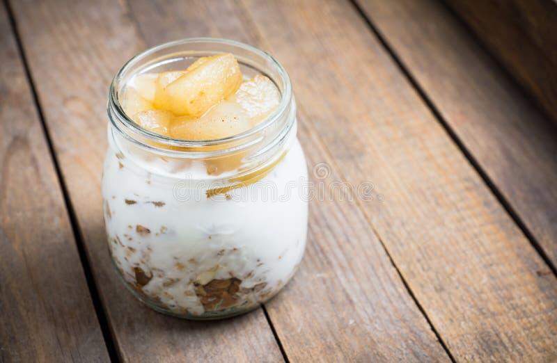 Sund och smaklig frukost med mysli, yougurt och grillade päron royaltyfria bilder