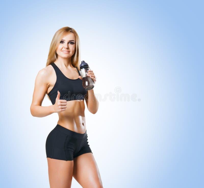 Sund och sportig flicka för passform, i sportswear över blå bakgrund arkivbild