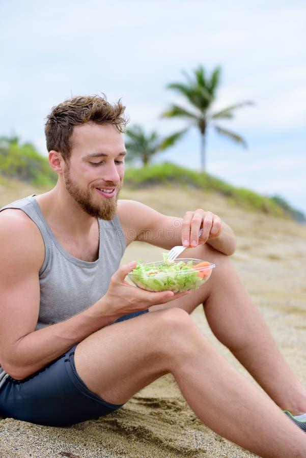 Sund passformman som äter organisk strikt vegetarianmat på stranden royaltyfri foto