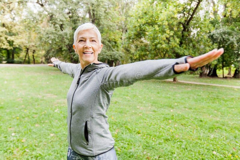 Sund pensionärpassformkvinna som gör konditionövning i natur royaltyfria foton