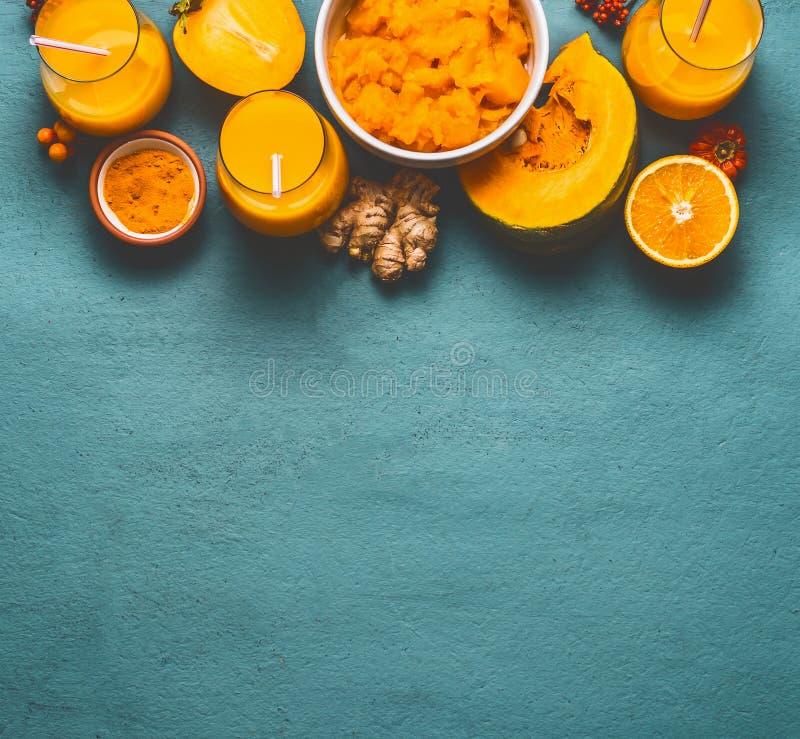 Sund pumpasmoothie i exponeringsglas med orange färgingredienser: persimon, orange frukt-, ingefära- och gurkmejapulver på blått arkivfoto