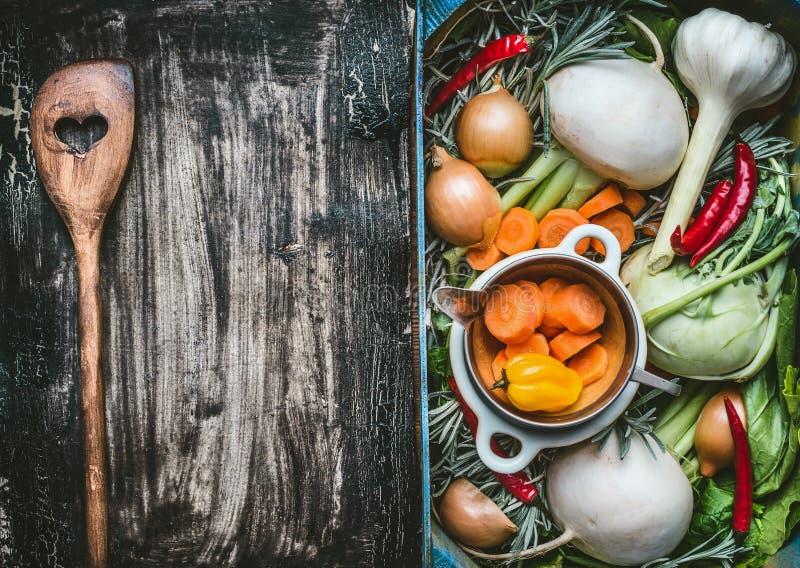 Sund ren matbakgrund med olika organiska nya grönsaker i en spjällåda och en trämatlagningsked med hjärta på mörkt lantligt royaltyfria bilder