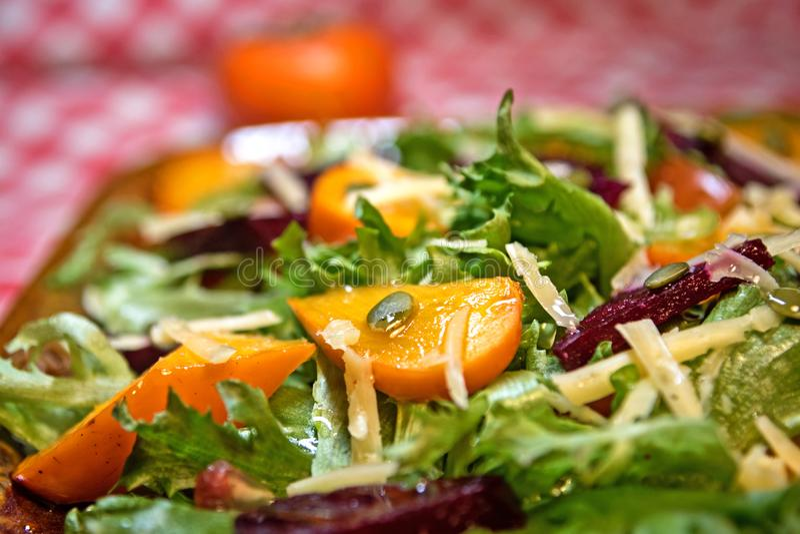 Sund sallad med den grönsallatsallad, persimonet och beta Persimonsallad banta Vegetarisk mat royaltyfri bild