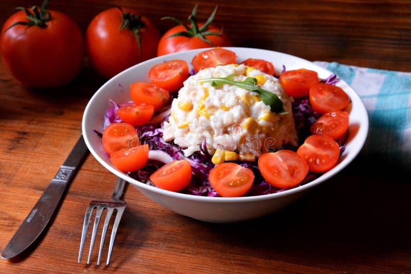 Sund salladplatta med vita ris, havre, körsbärsröda tomater och dressingen för röd kål på träbakgrundsslut upp Mat och hälsa royaltyfria foton