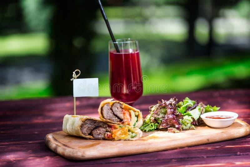 Sund shawarmasmörgås med nötkött, grön sallad, sås och lemonad På klippträbrädet och grön sommar arkivfoton