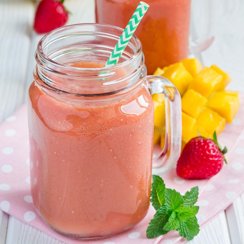 Sund smoothie med jordgubben, mango och bananen i exponeringsglaskrus, fyrkant arkivbild