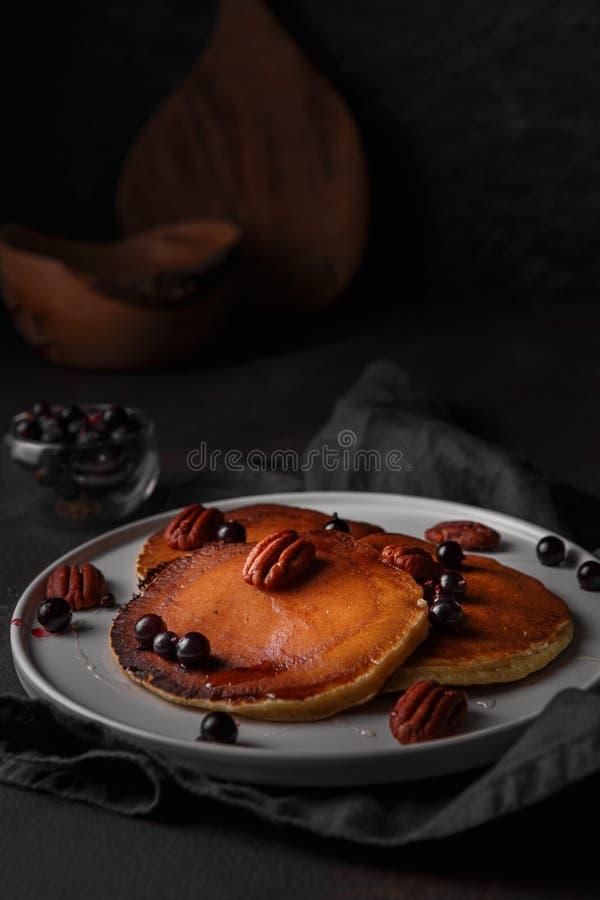Sund sommarfrukost, hemlagade klassiska amerikanska pannkakor med det nya b?ret, muttrar och honung p? m?rk bakgrund royaltyfria foton