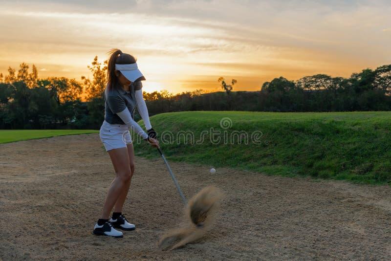 sund sport Asiatisk sportig fälla för sand för kvinnagolfarespelaren och chipskottet under hans runda i bankiren, gör hon förmodl royaltyfria foton