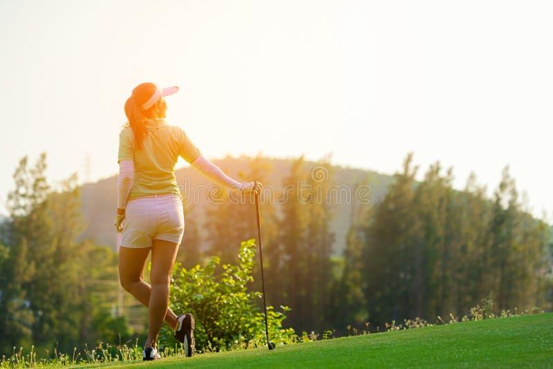 Sund sport Asiatisk sportig kvinna för golfare att koppla av på farleden för den satta golfbollen på den gröna golfaftontiden i s royaltyfria foton