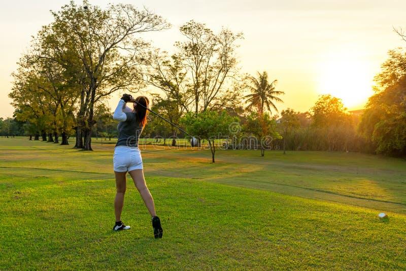 sund sport Den asiatiska sportiga kvinnagolfarespelaren som g?r golfgungautslagsplatsen av p? den gr?na aftontiden, ?var hon f?rm fotografering för bildbyråer