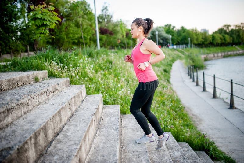 Sund spring för livsstilsportkvinna på gatatrappa längs ri royaltyfria bilder