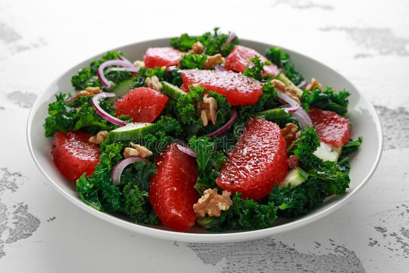 Sund strikt vegetarian, vegetarisk grapefruktgrönkålsallad med valnötter, röd lök och gurka på vit bakgrund royaltyfria bilder