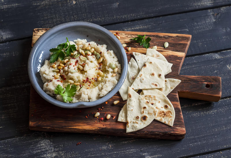 Sund strikt vegetarianblomkålhummus och hemlagad tortilla på en mörk lantlig skärbräda på en mörk bakgrund royaltyfria bilder