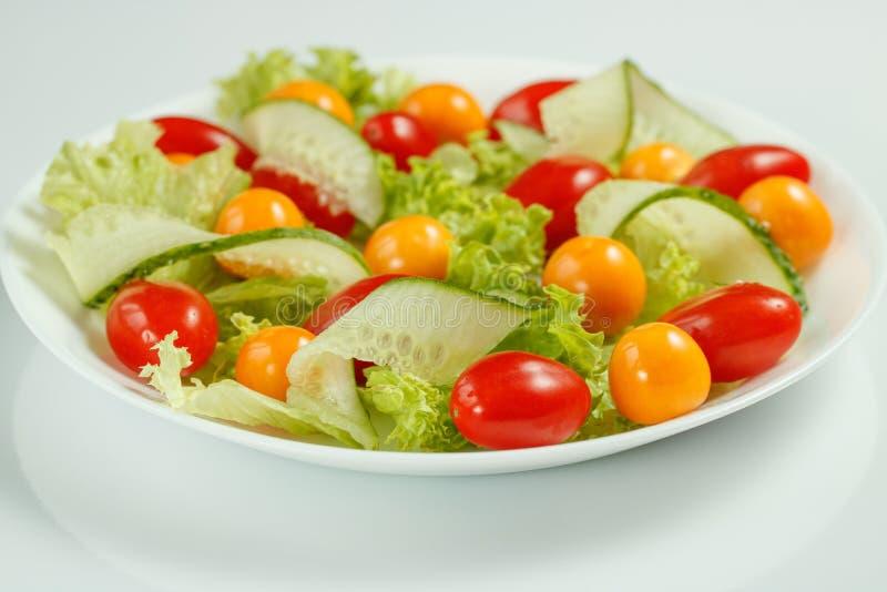 Sund strikt vegetarianlunch med grön sallad och röda gula tomater royaltyfri fotografi