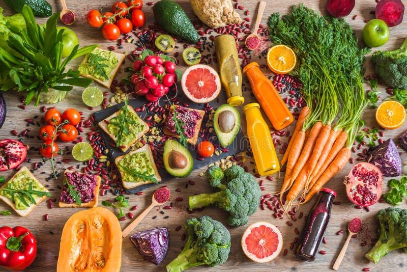 Sund strikt vegetarianmat Smörgåsar och nya grönsaker på träbakgrund Detoxen bantar Olika färgrika nya fruktsafter Top beskådar royaltyfri foto