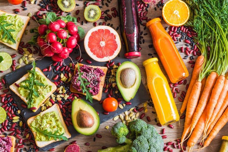 Sund strikt vegetarianmat Smörgåsar och nya grönsaker på träbakgrund Detoxen bantar Olika färgrika nya fruktsafter Top beskådar arkivbilder