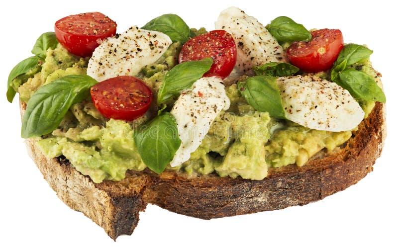 Sund strikt vegetariansmörgås med avokadot, mozzarellaen, tomater och basilika arkivfoto