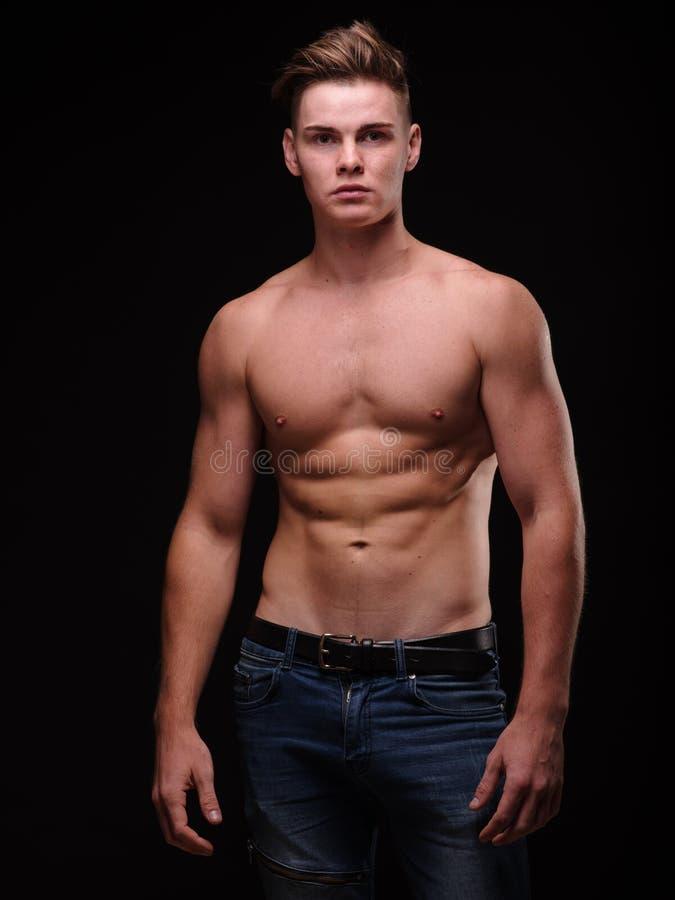 Sund tonårs- grabb som är shirtless på en svart bakgrund Sportiga unga män Muskelbyggnadsbegrepp royaltyfria foton