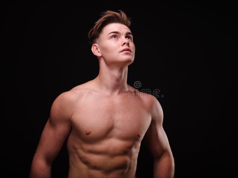 Sund tonårs- grabb som är shirtless på en svart bakgrund Sportiga unga män Muskelbyggnadsbegrepp royaltyfri foto