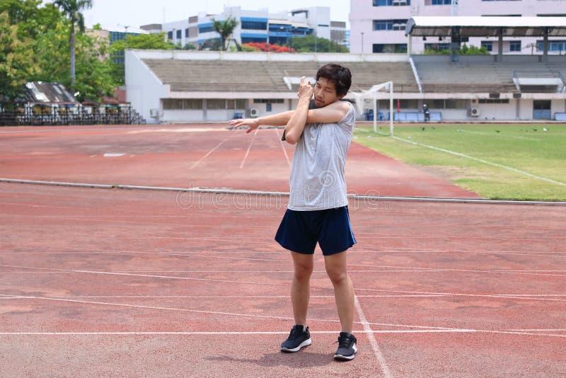 Sund ung asiatisk löpareman som värmer upp för körning på spår i stadion fotografering för bildbyråer