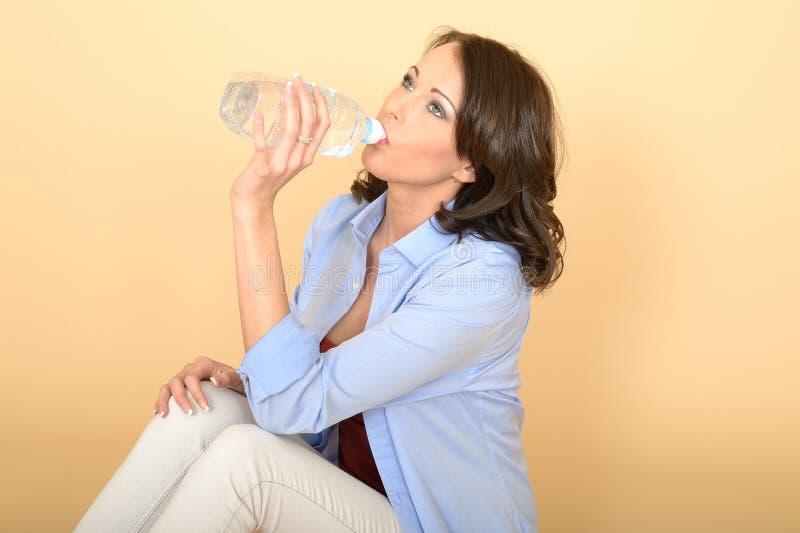 Sund ung kvinna som dricker en flaska av ny mineralvatten arkivbilder