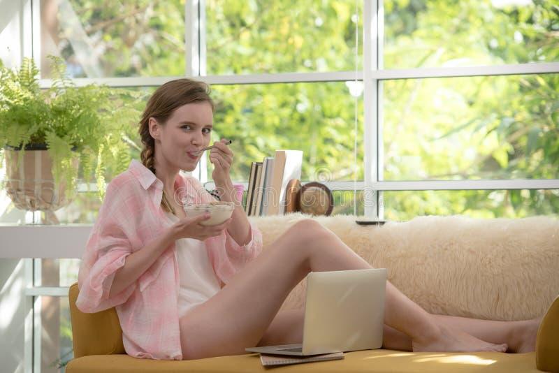 Sund ung kvinna som ligger på en soffa som äter yoghurten som ser avkopplad och bekväm arkivfoto