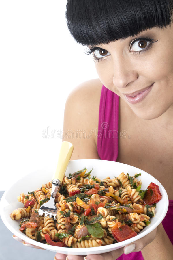 Sund ung kvinna som rymmer en färgglad bunke av tomat- och grönsakpasta arkivbild