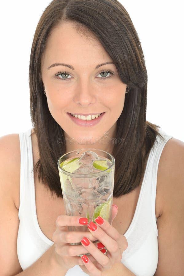 Sund ung kvinna som rymmer ett exponeringsglas av lugnt vatten med is och limefrukt royaltyfri foto