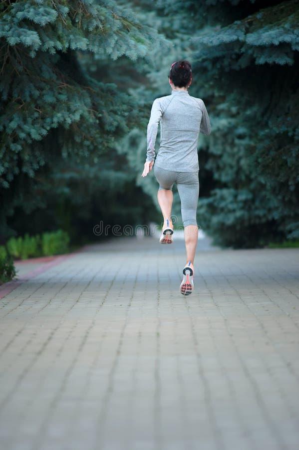 Sund ung spring för löpare för konditionkvinnaslinga på parkera lodisar royaltyfri bild